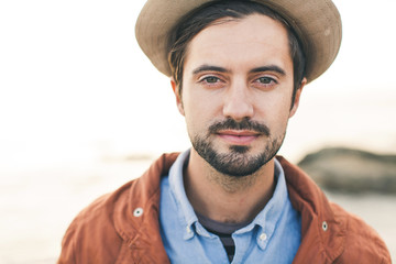 Portrait of stylish man wearing a hat at the beach