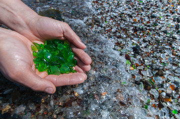 Womans hands hold up a collection of green sea glass