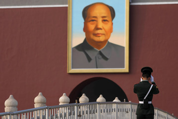 A paramilitary policeman adjusts his hat in front of a giant portrait of late Chinese chairman Mao Zedong at the Tiananmen Gate during the 19th National Congress of the Communist Party of China in Beijing