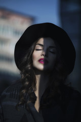Young beautiful woman with curly hair, hat and red lipstick