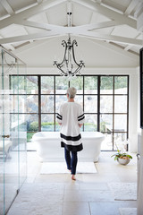 Rear view of woman walking towards bathtub in her bathroom