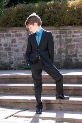 Junge steht lässig im Anzug