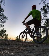 Mountain biker looking at sunset, bike trail in autumn mountains