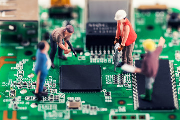 electronics repair and tech support concept - workers repairing circuit board
