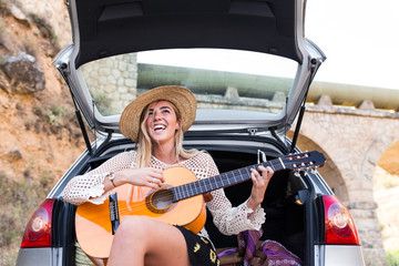 Woman playing guitar on a car