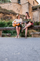 Women with guitar on roadside