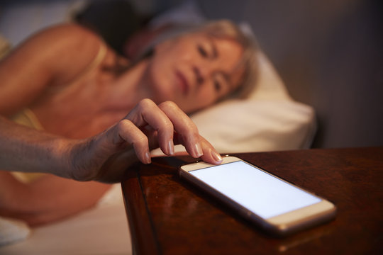 Sleepless Senior Woman In Bed At Night Checking Mobile Phone