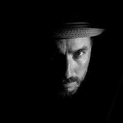 Dark lit portrait of a man and his face with a fedora hat