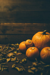 Bunch of pumpkins on wooden background with leaves