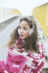 Portrait of a young woman wrapped in red Christmas blanket outdoors