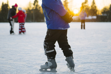 child ice skates outside on a winter afternoon