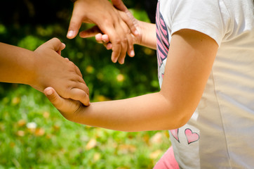 young girl joining hands with her mother to play in bright sunny day