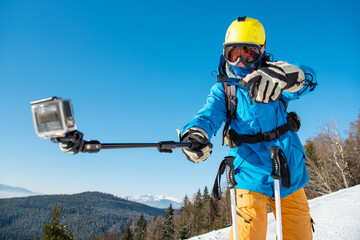 Horizontal shot of a male skier having fun outdoors taking a selfie with action camera on a monopod modern technology active lifestyle concept