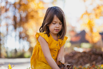 Girl wearing gold top gather leaves