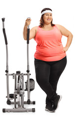 Overweight woman with a cross trainer machine