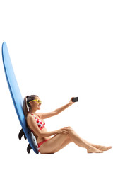 Young woman leaning against a surfboard and taking a selfie