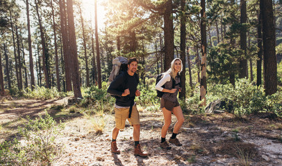 Hiking couple walking in forest wearing backpacks Wall mural