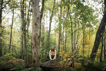 girl crouches in a New England forest