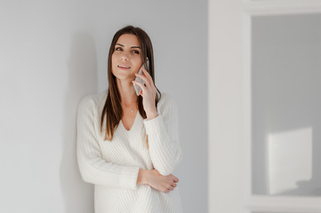 Smiling young beautiful woman in elegant white interior home, talking on mobile phone, looking at camera and smiling.