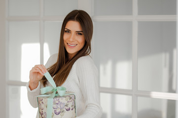 Delicate young woman in elegant white interior home, holding a beautiful present round box, pulling the ribbon and opening the present, looking and smiling at camera.