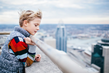 boy looks down at the city from the top of a building