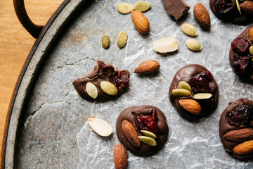 Chocolate with cranberry, almonds and pumpkin seeds on a stone tray from above
