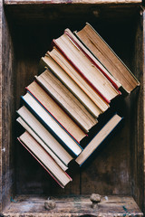 Old hardcover books in a wooden box