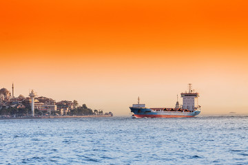 Empty container cargo ship in Istanbul Bosporus harbor at sunset