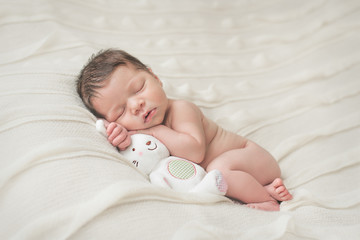 Newborn baby girl lying and sleeping on a blanket