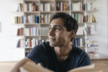 Smiling young man with book at home looking sideways
