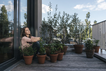 Woman relaxing on balcony surrounded by plants