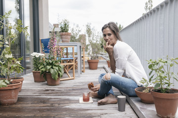 Smiling woman eating croissant with jam on balcony