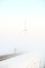 Walking man and windmill in dense fog in the winter