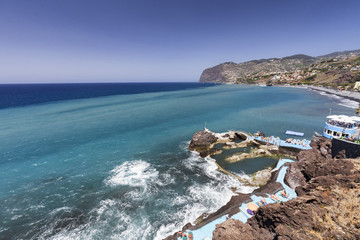 Different colored waters behind ocean water pools in Sao Martinho on the island of Madeira, Portugal.