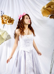 young woman dressed as Alice in Wonderland with big playing card and flowers