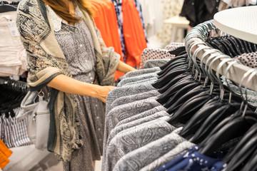 woman choosing clothes at shopping mall