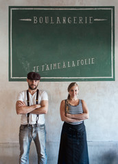 Young Male and Female Baker Standing With Crossed Arms in Front of Shabby Wall