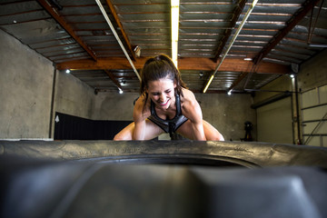 Fit female athlete lifting tire during extreme cross training exercise with emotion and intense expression