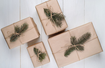 Christmas background with gift boxes wrapped in kraft paper with fir tree branches on white wooden background, free space. Holiday greeting card, copy space. Flat lay, top view