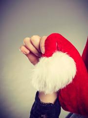 Woman holding white pompon on Santa hat