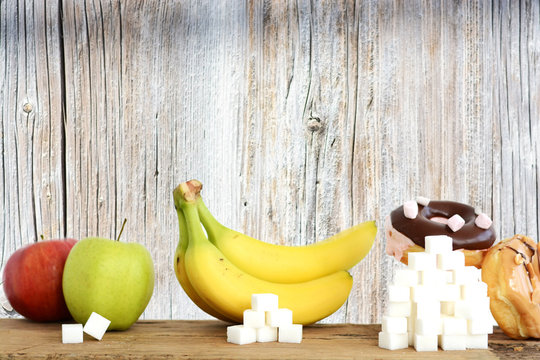Analyzing the quantity of sugar in different foods, suggested by piles of sugar cubes in front of fruits and desserts on wooden background