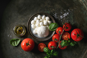 Spoed Fotobehang Buffel Ingredients for italian caprese salad. Mozzarella balls, buffalo in metal vintage plate, tomatoes, basil leaves, olive oil with vinegar over dark background. Top view with space. Rustic style