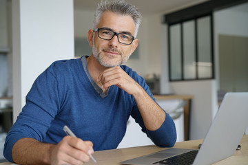 Middle-aged man working from home-office on laptop