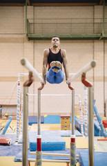 Male gymnast performing on gymnastic rings