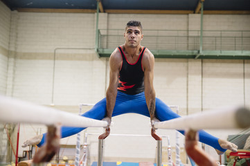 Male gymnast performing on gymnastic rings