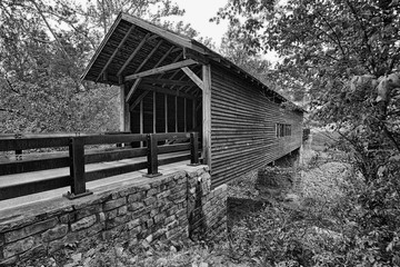 Covered wooden bridge over mountain stream in black and white