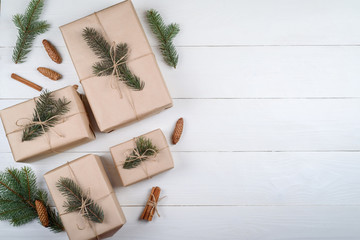 Christmas background with gift boxes wrapped in kraft paper with fir tree branches and cones on white wooden background, free space. Holiday greeting card, copy space. Flat lay, top view