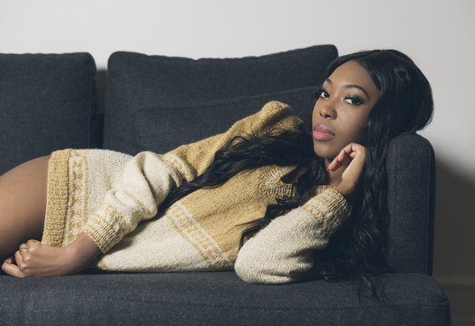 Young attractive black woman making eye contact while lying on a couch
