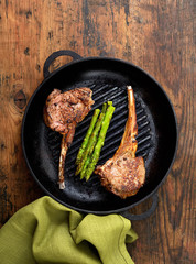 grilled lamb steak with asparagus in a frying pan on a wooden background