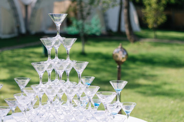 Champagne glass pyramid. Pyramid of glasses of wine, champagne, tower of champagne's glass in wedding reception party. Summertime, green grass background